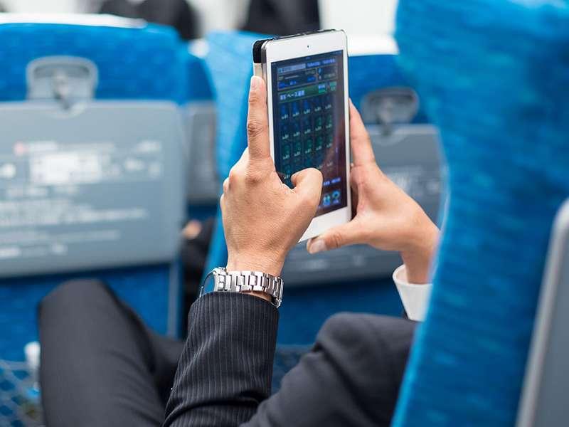 在飞机上使用平板电脑电话的商人